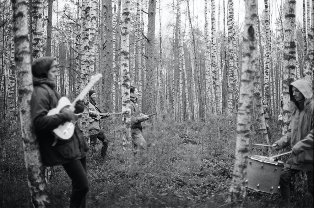 grayscale photo of playing middle bare tree