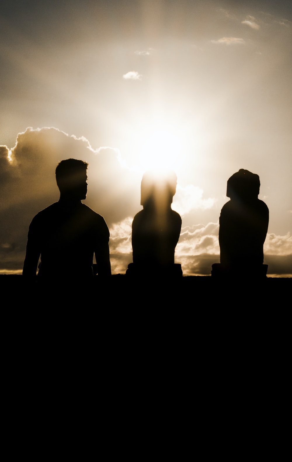 silhouette of three person during golden hour