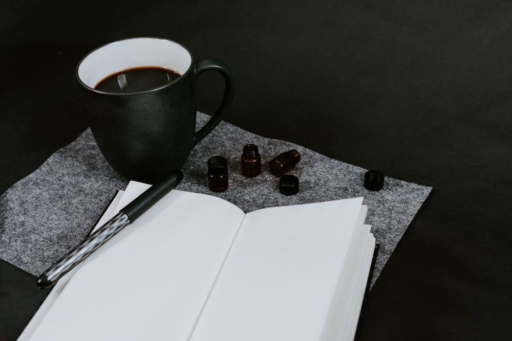 opened empty book beside cup of coffee