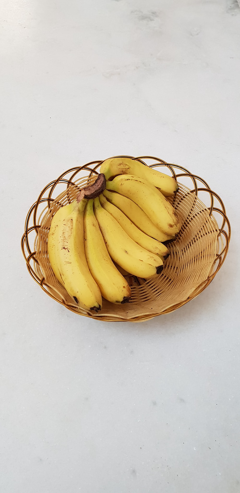 bunch of yellow bananas in a brown wicker bowl