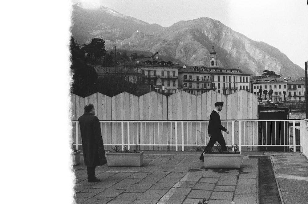 men walking beside fence