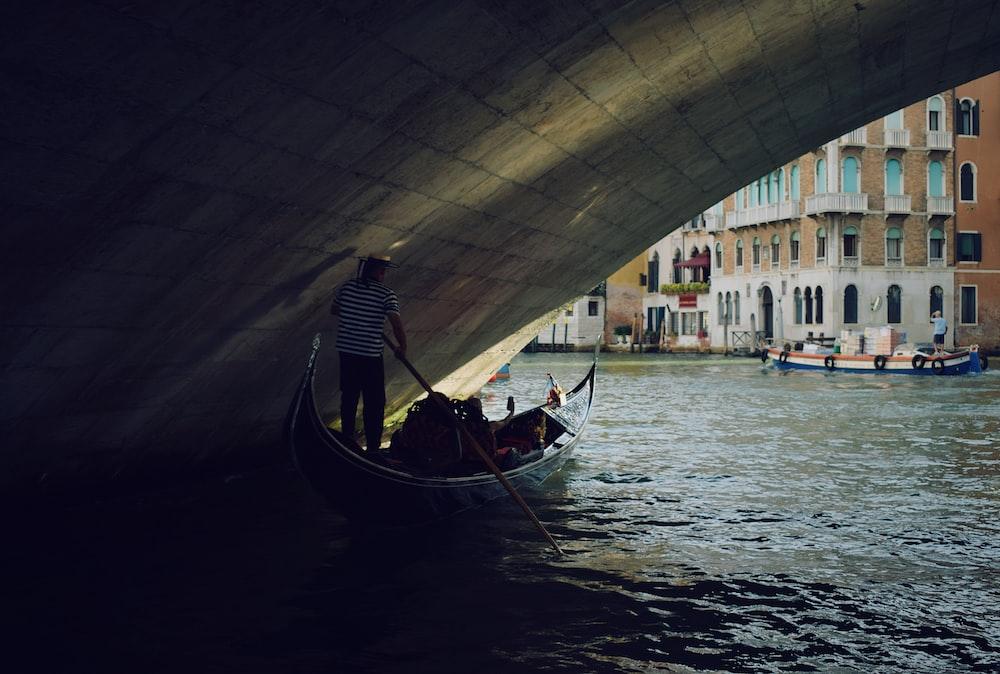 man riding boat under bridge during daytime