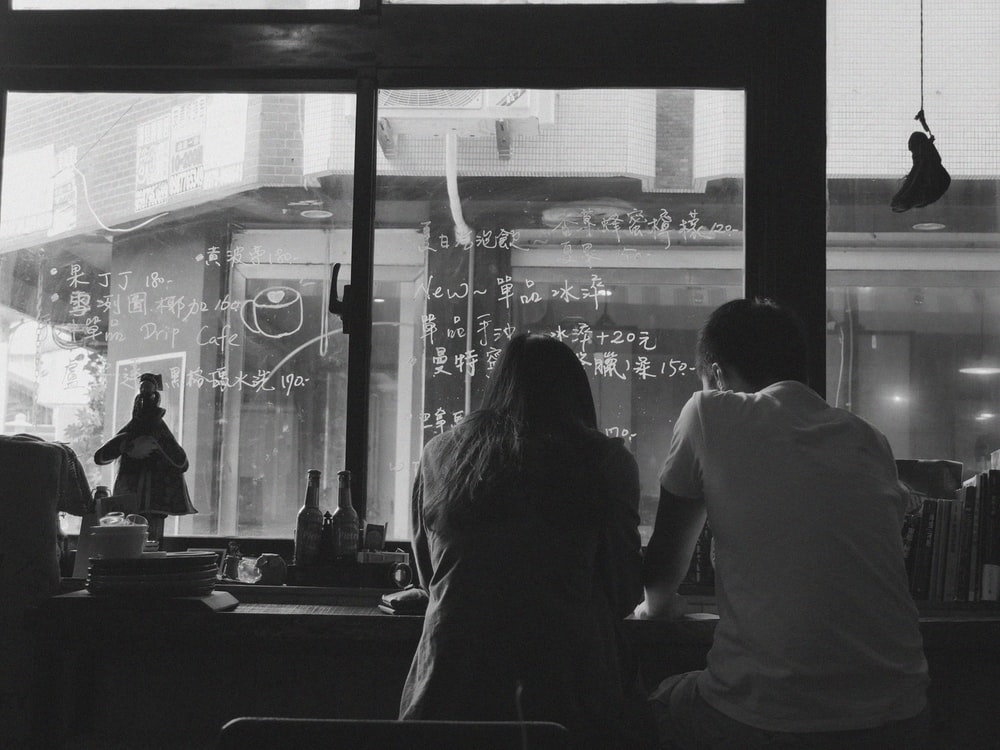 man and woman sitting near window