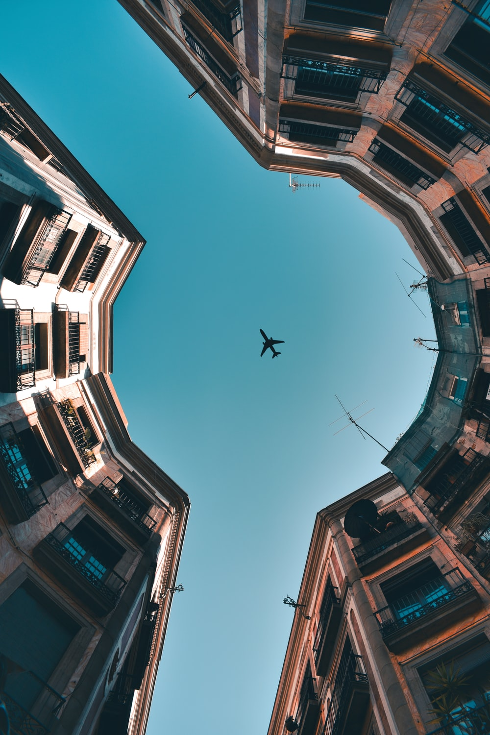 worm's eye view of brown buildings and an airplane in flight