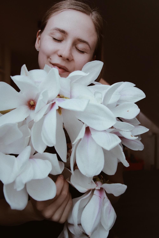 woman holding white-petaled flower