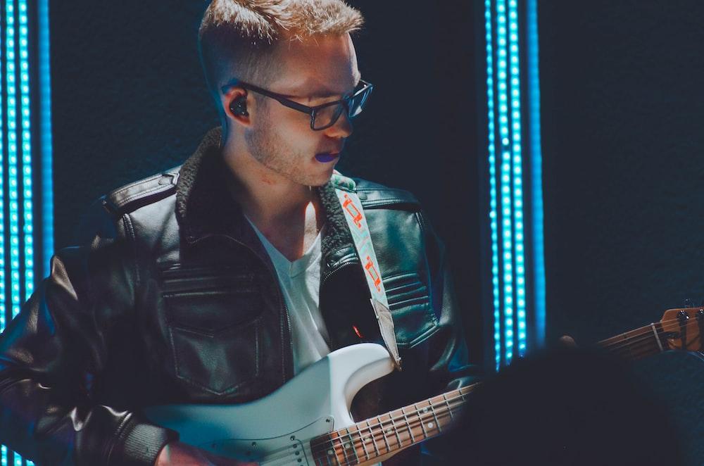 man playing white guitar