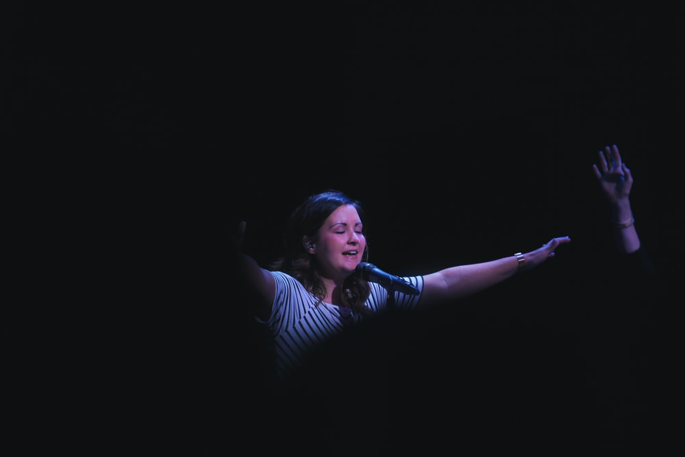 woman singing on stage raising her hands