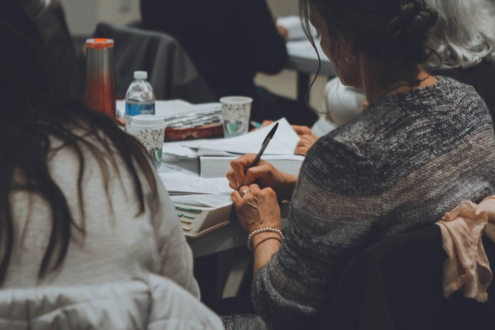 woman wearing grey shirt writing on white paper