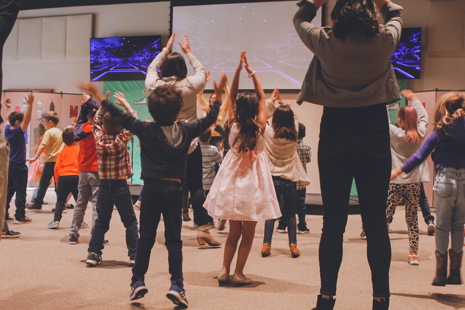 women and children dancing inside room