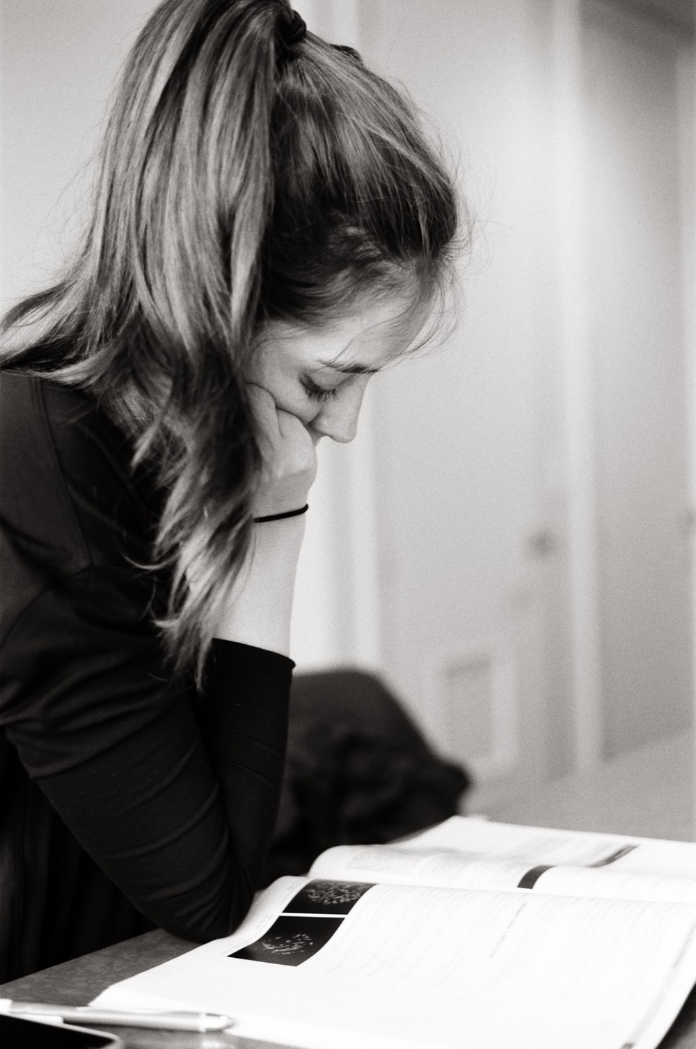 woman resting her head on her right hand beside table with opened book