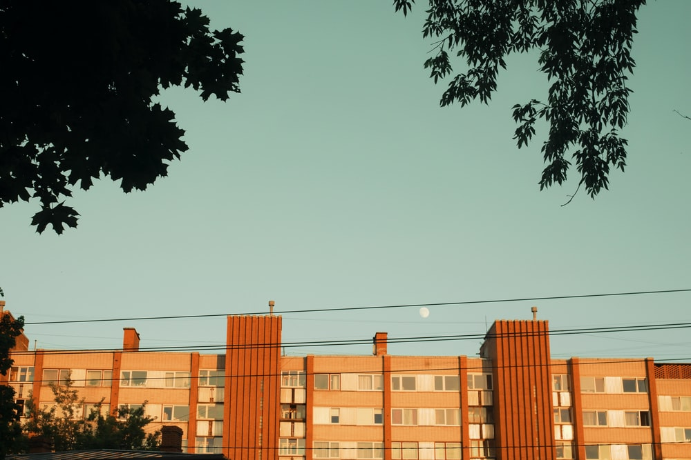 orange building near trees under clear sky