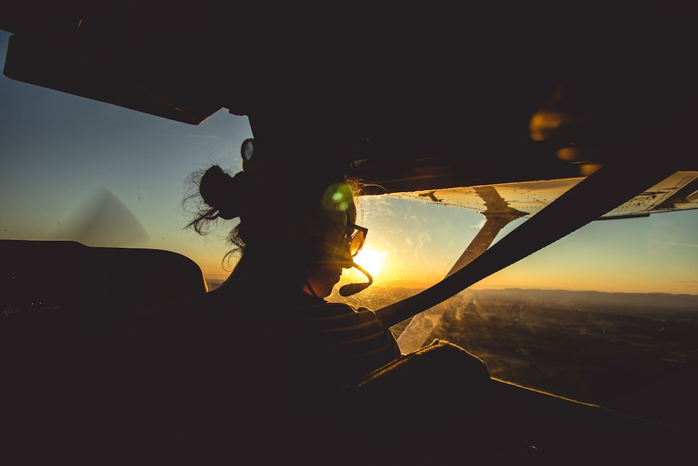 person driving plane close-up photography