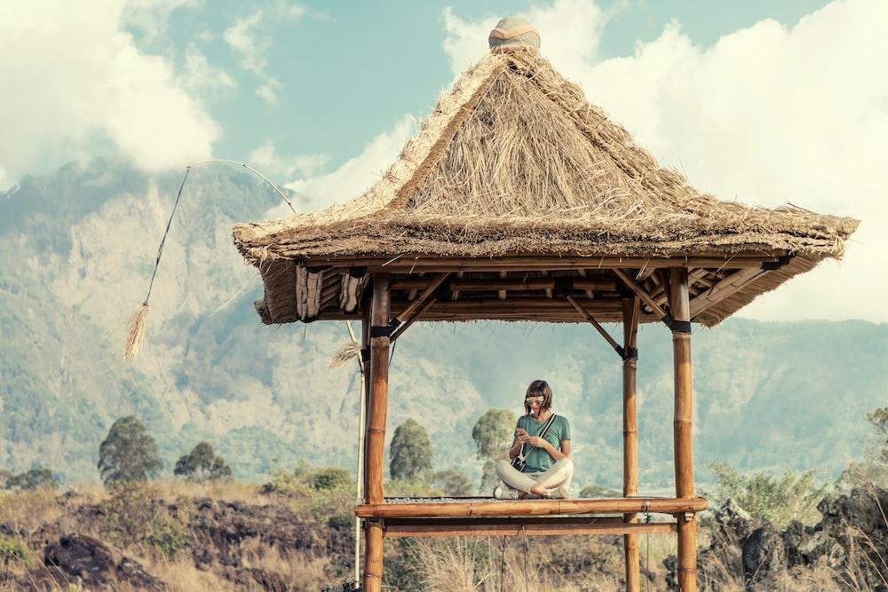 woman sitting in lotus position in floor of brown wooden hut
