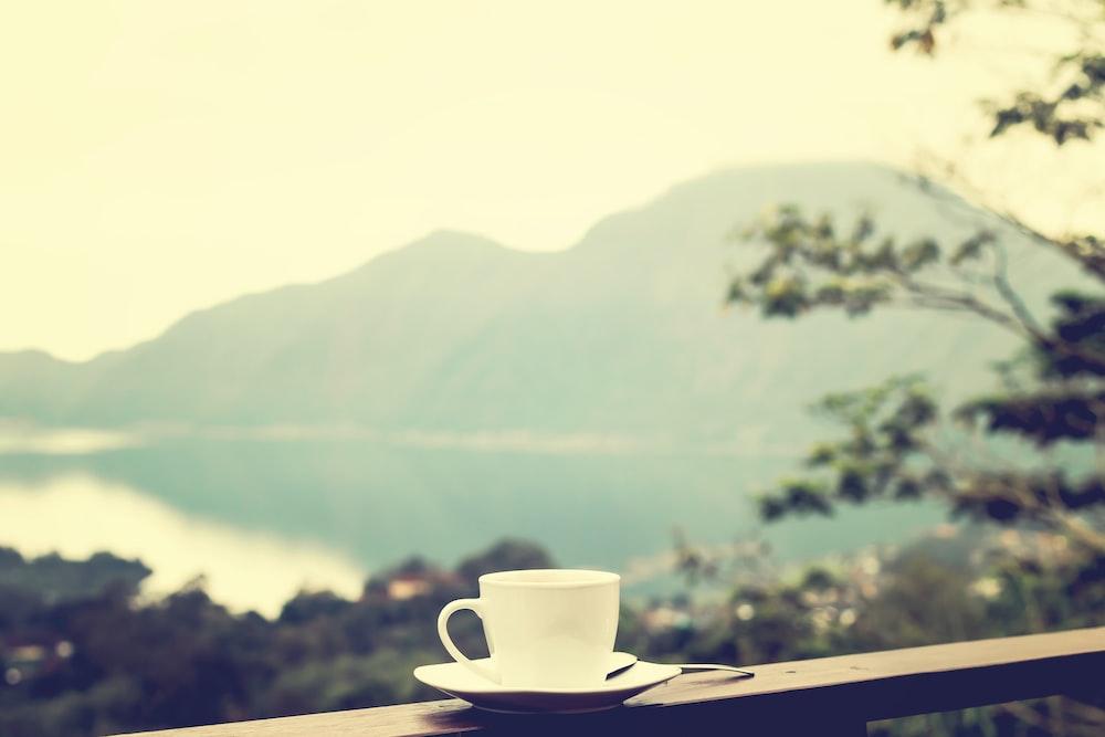 white ceramic mug on brown balcony