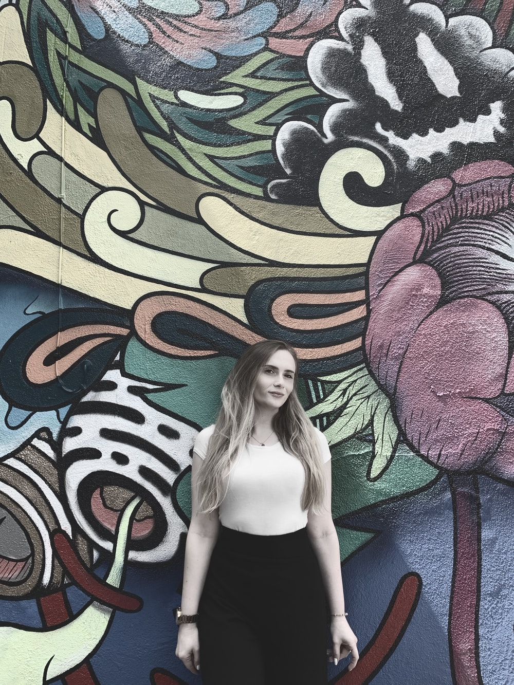 woman in white T-shirt standing in front of wall art