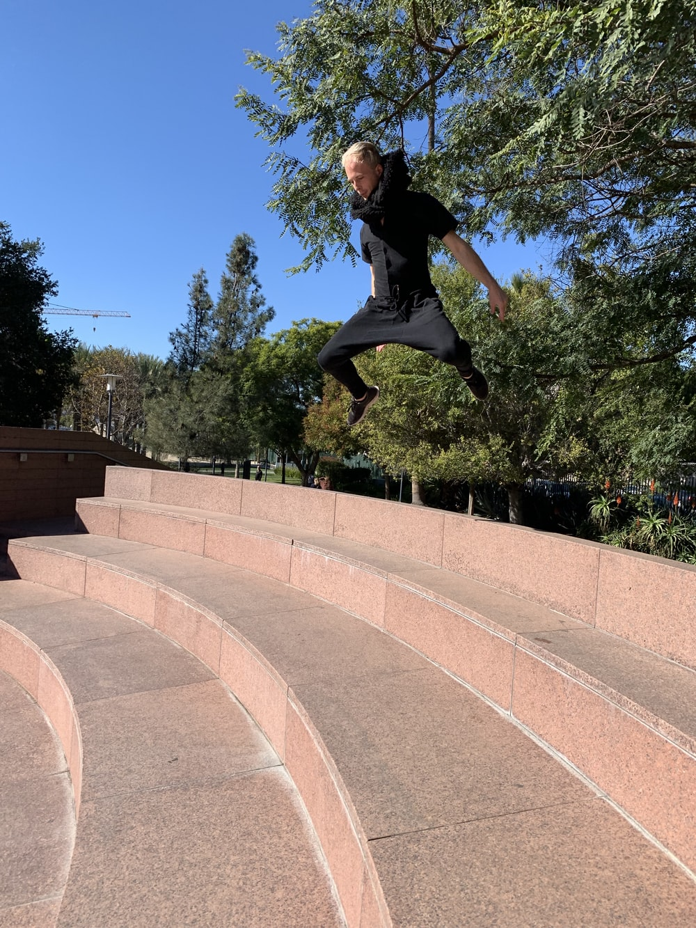 man in black jumping over stairs