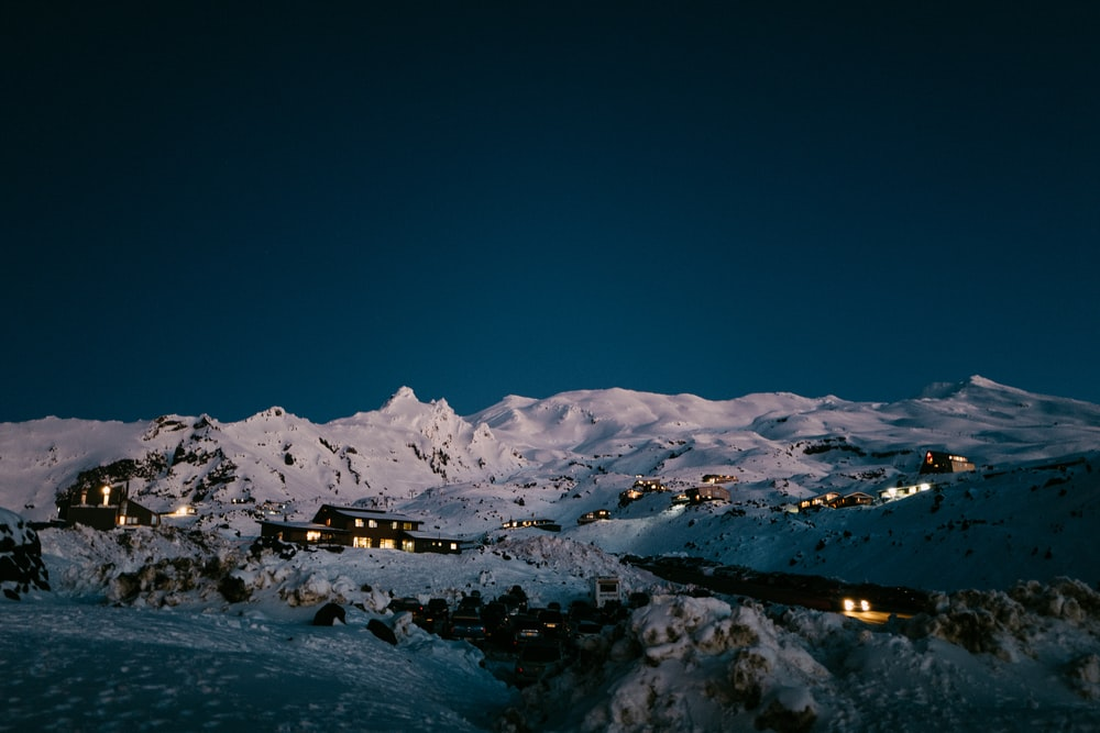 houses on snow-capped mountain during night
