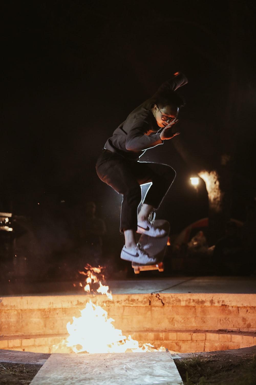 man in black jacket skateboarding near fire