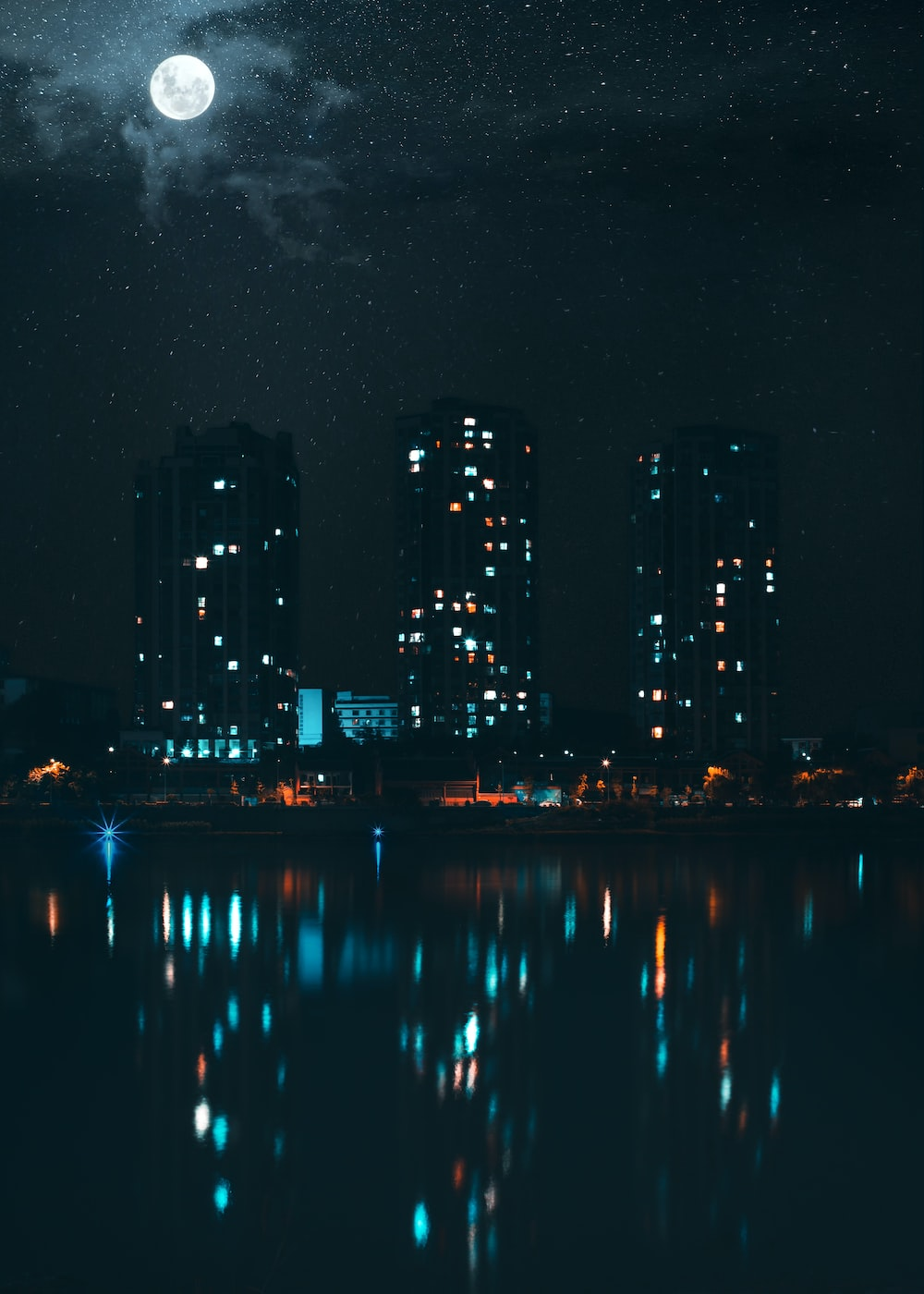 lighted building reflection on body of water during night