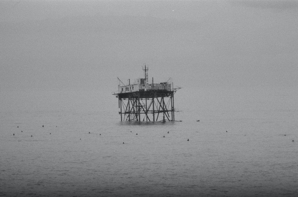 grayscale photography of building on sea