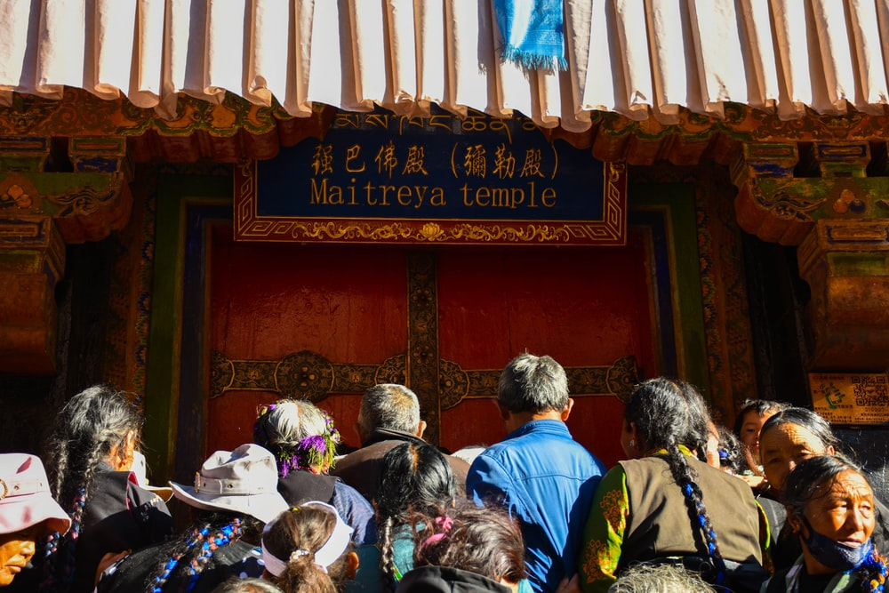 people gathering on front of Maitreya temple sign