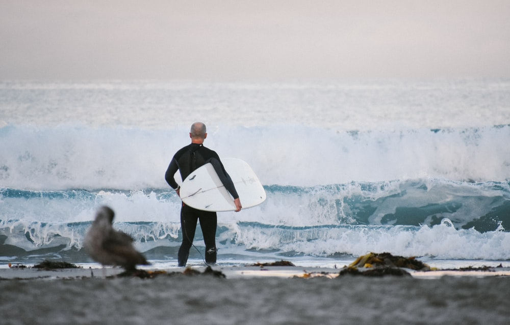 man standing and carrying surfboard facing the ocean wave during day