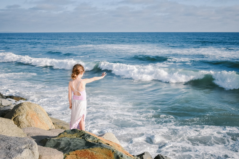 girl standing on cliff in front of body of water