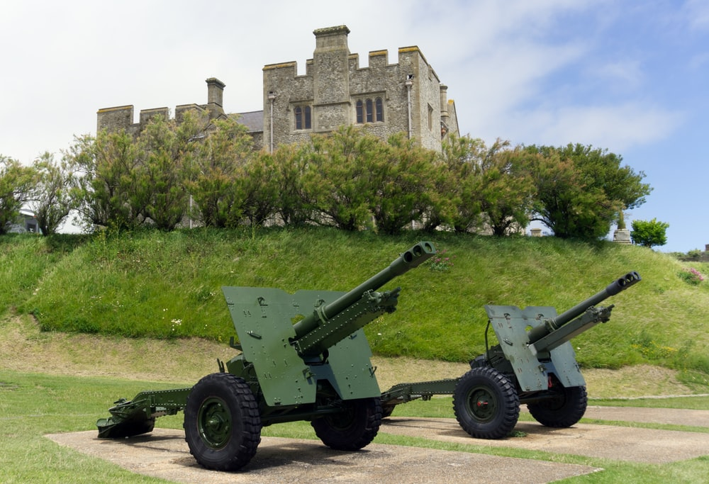 two green and gray machine guns near gray chateau