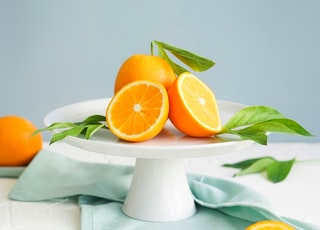 orange fruit in white ceramic plate close-up photography