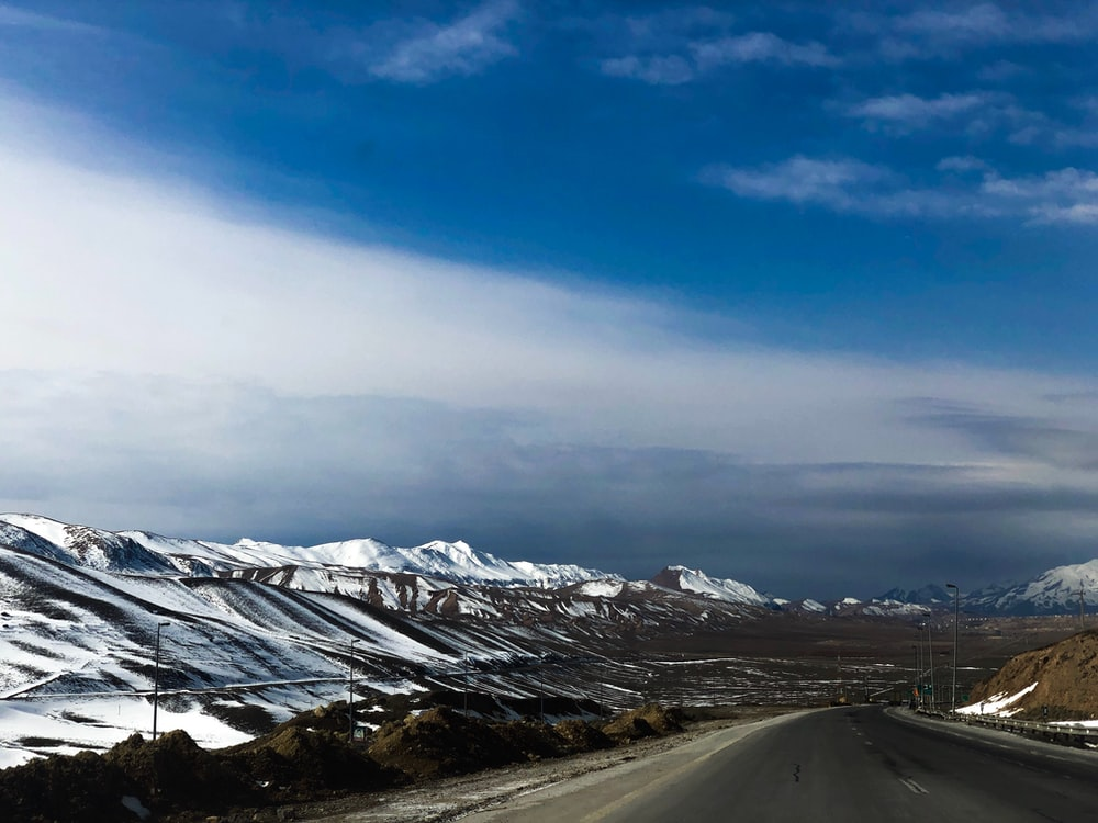 icy mountain and gray asphalt road