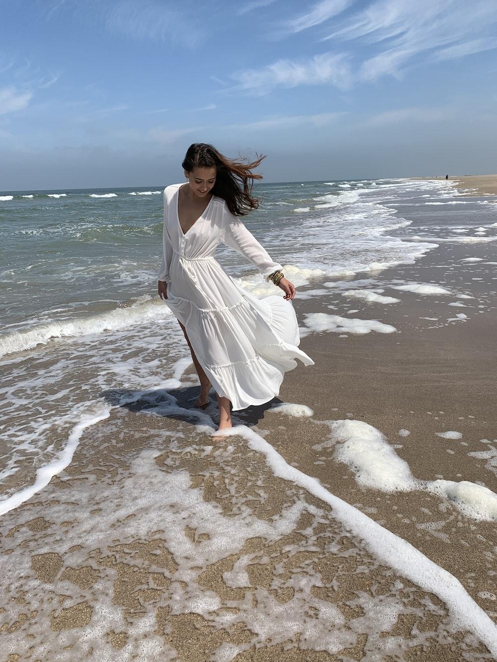 woman wearing white maxi dress at the beach