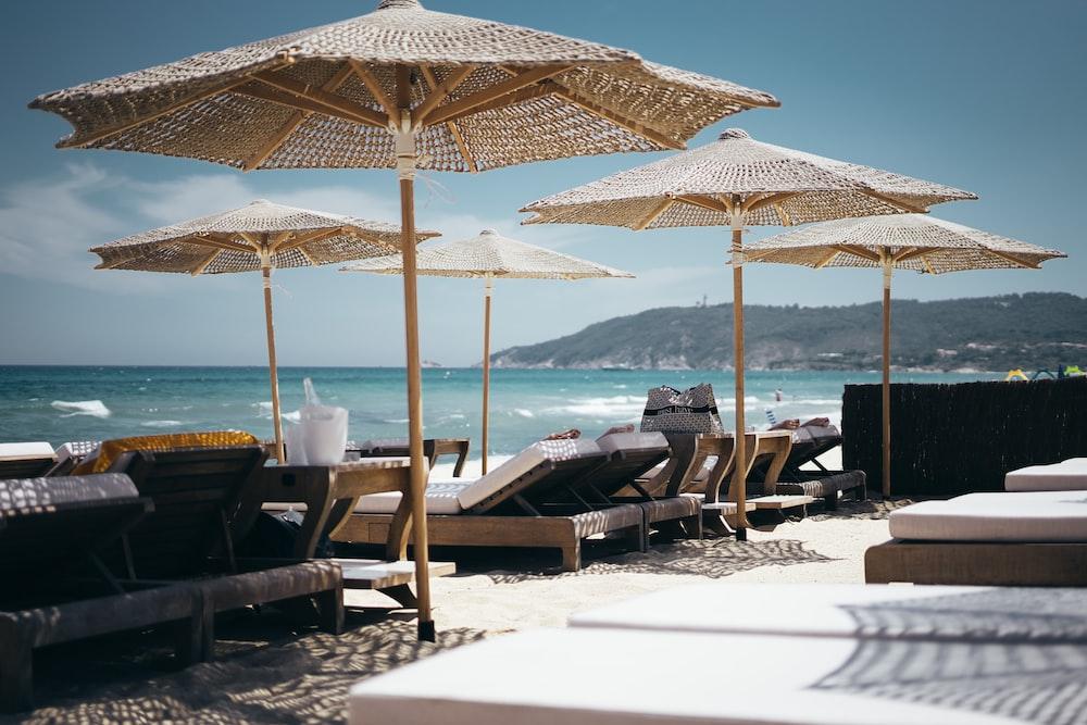 brown wooden sunloungers on beach