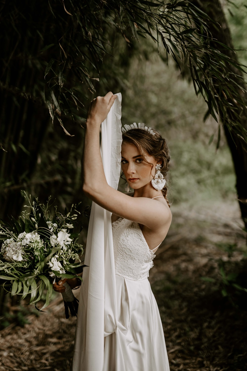 woman wearing white bridal gown across green forest