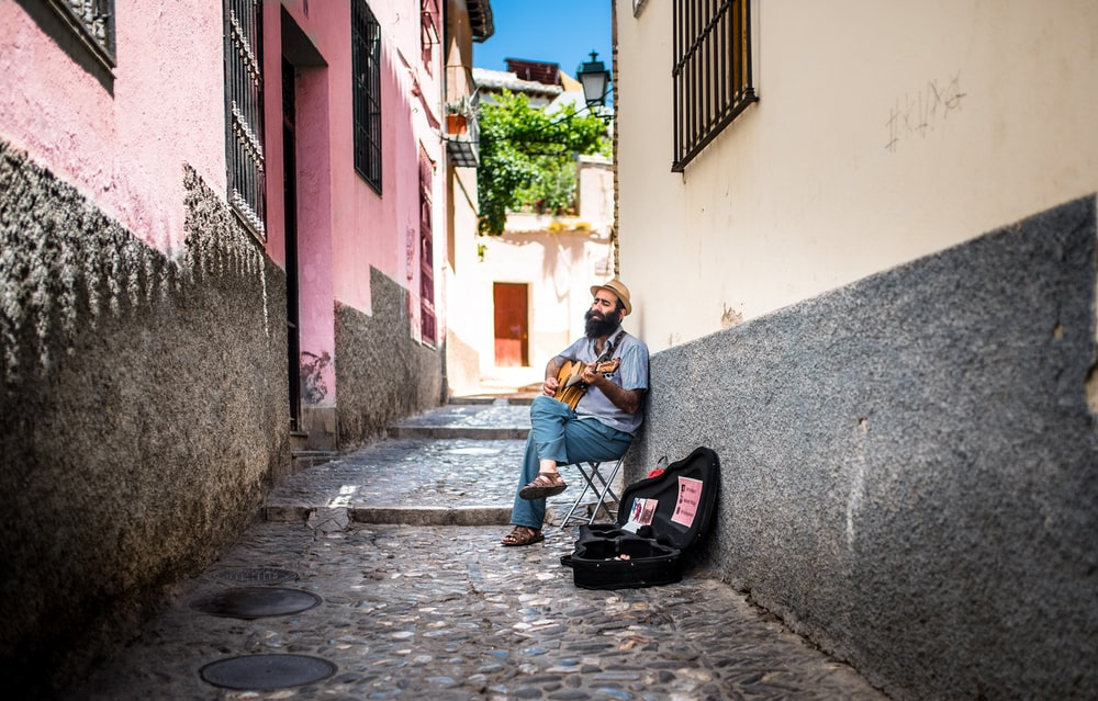 sitting man playing guitar with open guitar bag on side on allway