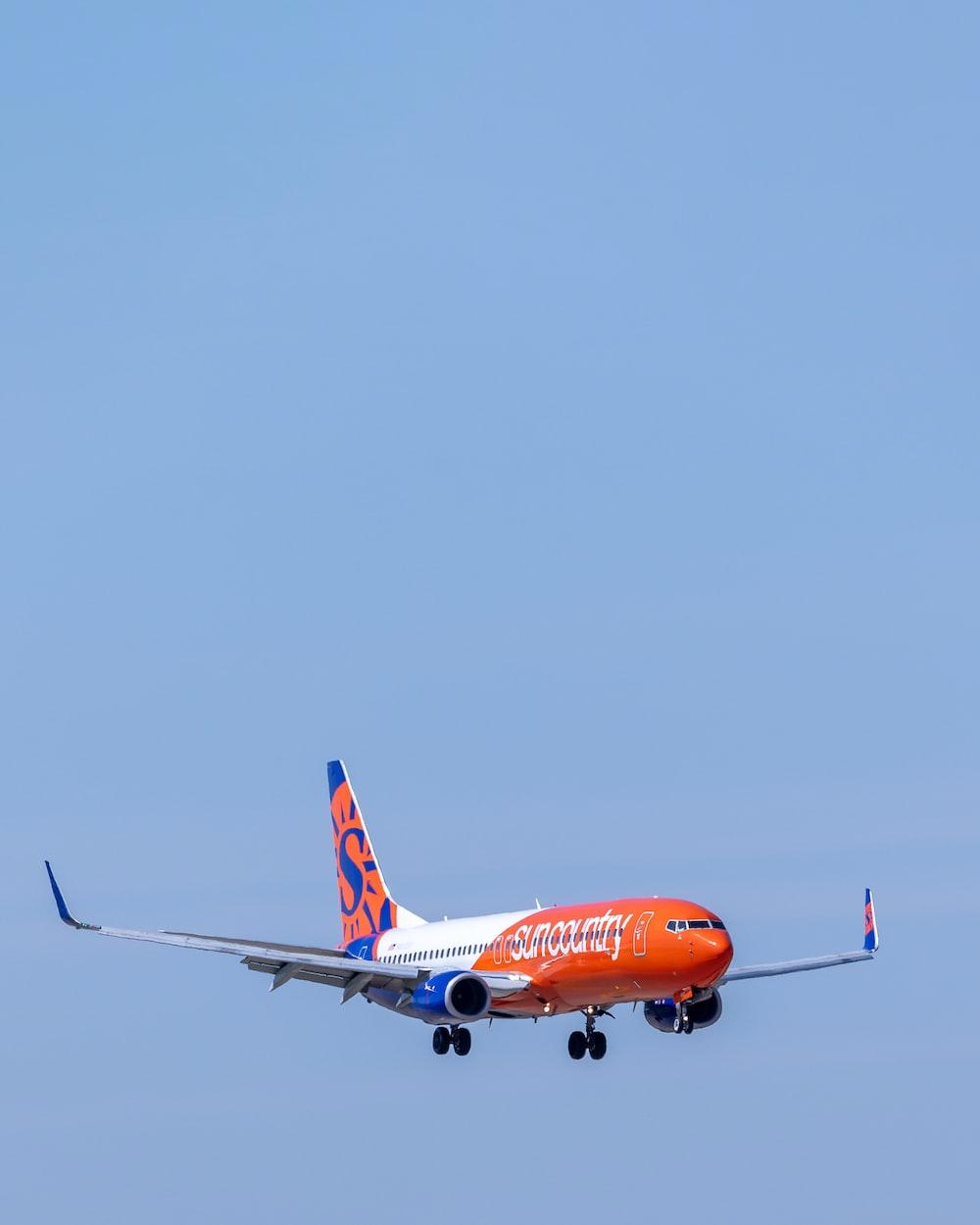 orange and white airplane on flight