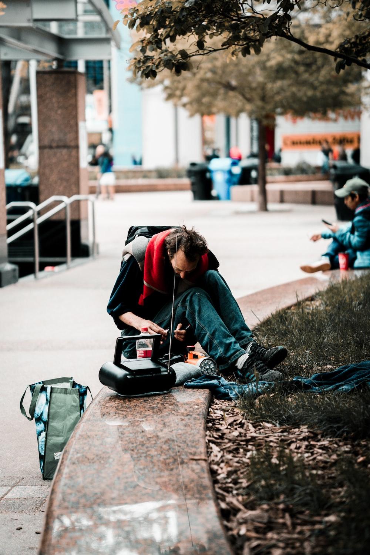 man wearing blue pants besides portable radio