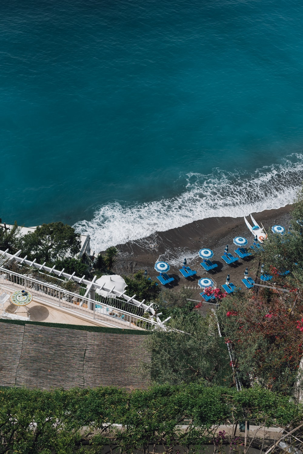 aerial photography of umbrellas and sunloungers by the beach