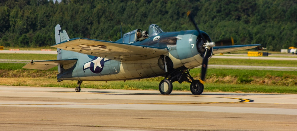 blue US vintage fighter plane taxiing at airport