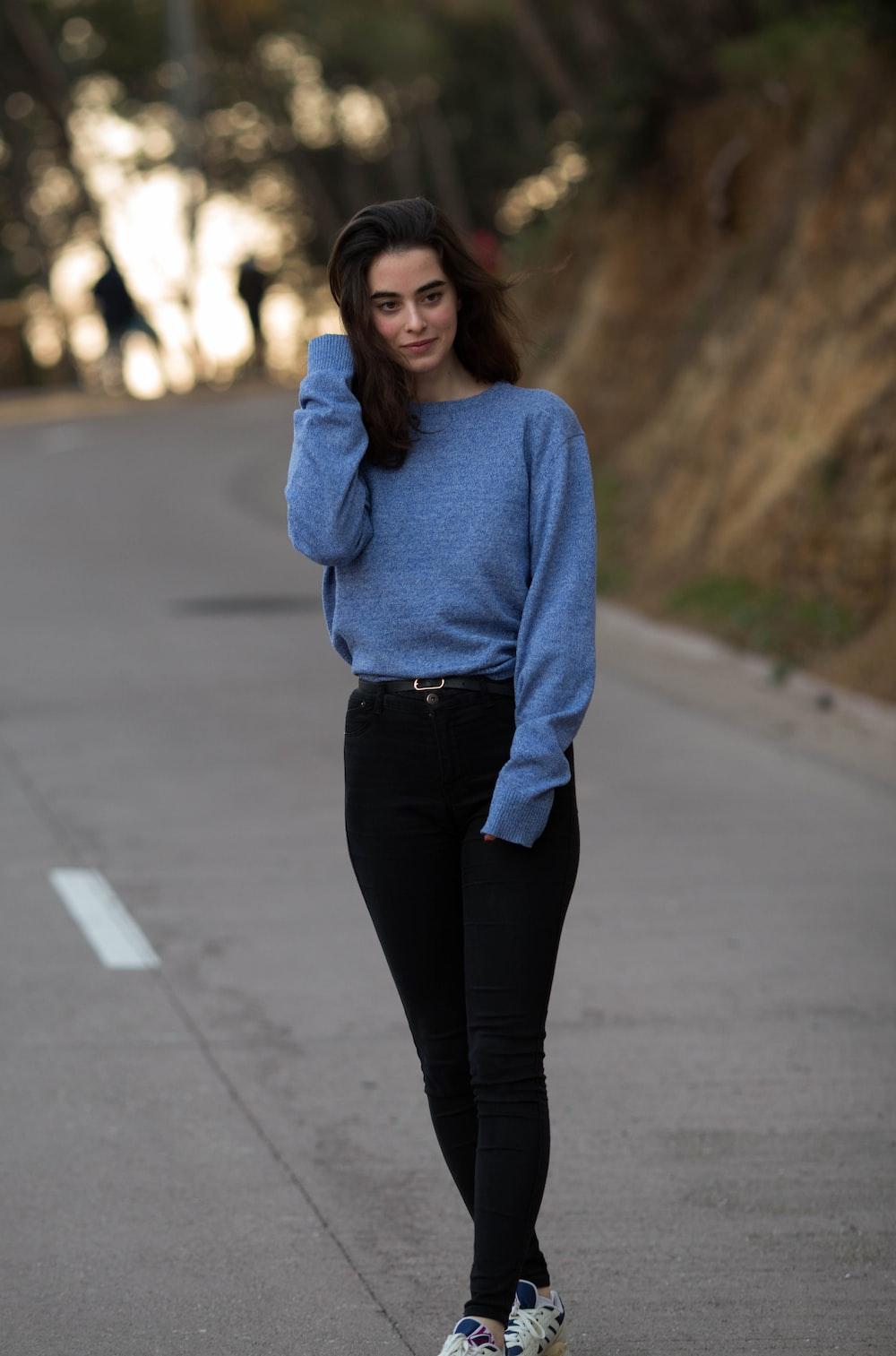 woman wearing blue sweatshirt and black straight-cut jeans \