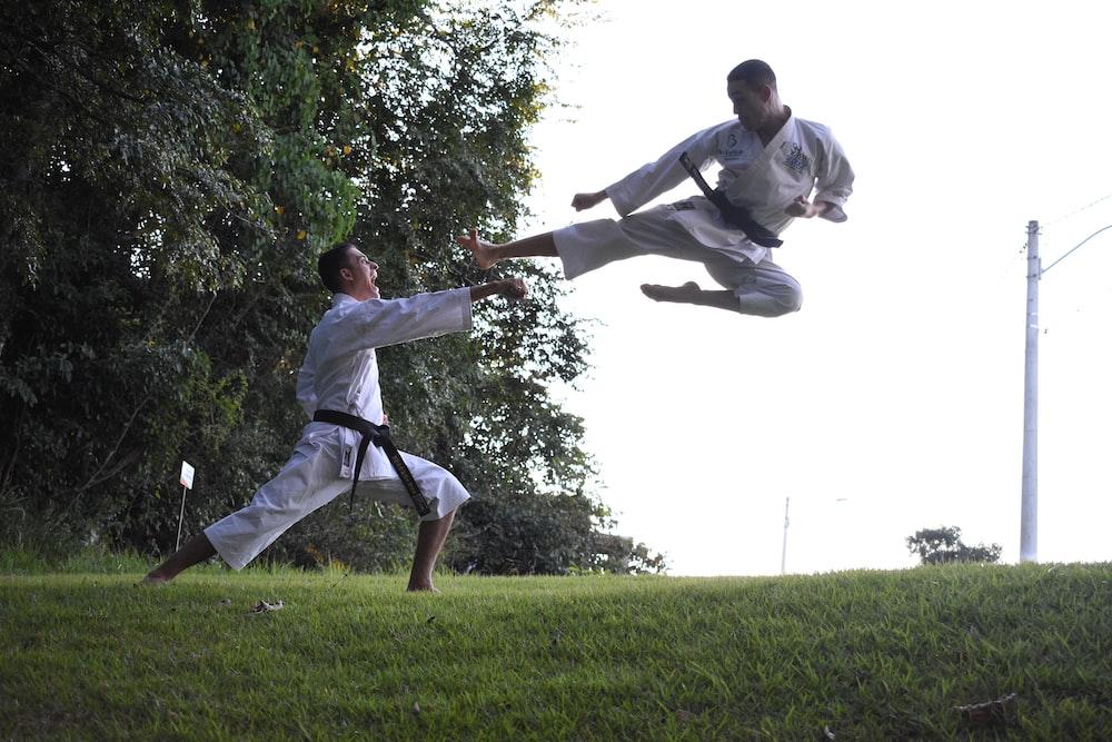 two men doing karate on green grass field