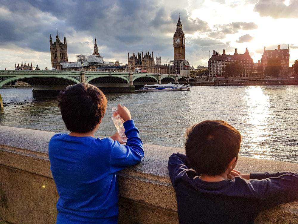 two boys watching golden hour near bridge