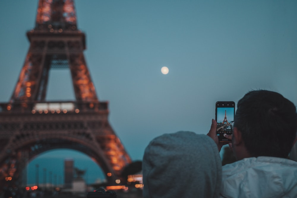 man taking picture of eiffel tower