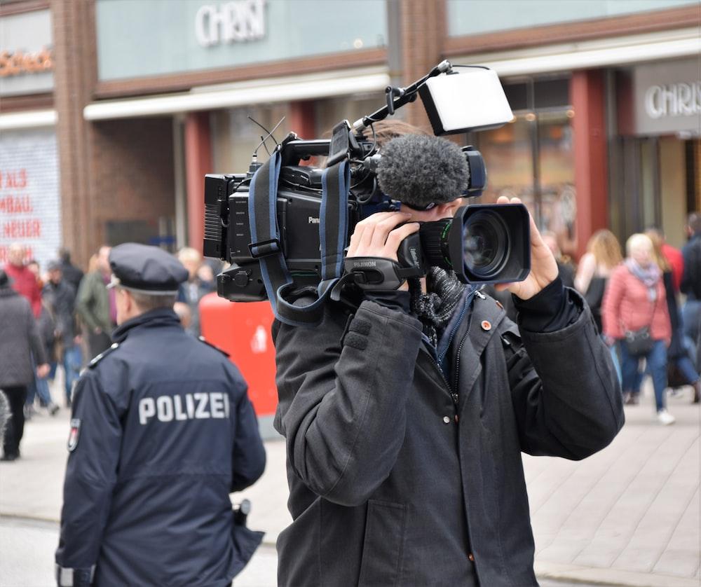 man holding shooting camera