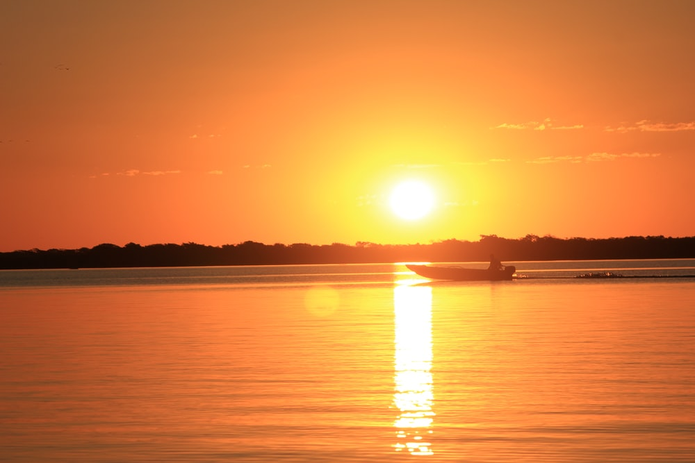 boat on calm body of water during golden hour