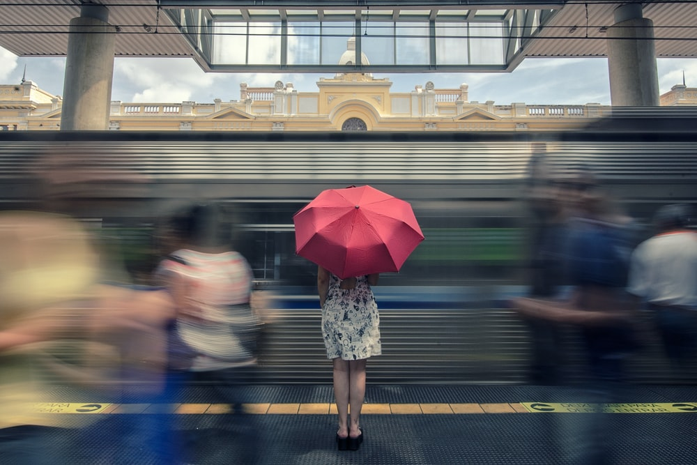 woman in floral dress under red umbrella