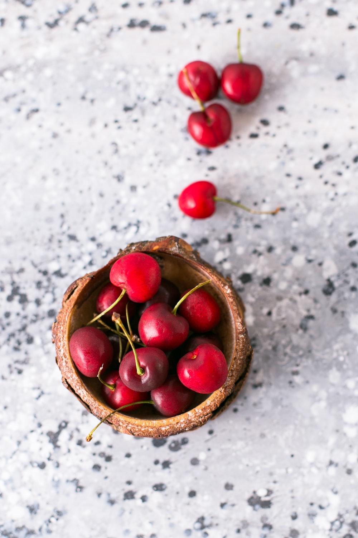 red cherries in brown bowl
