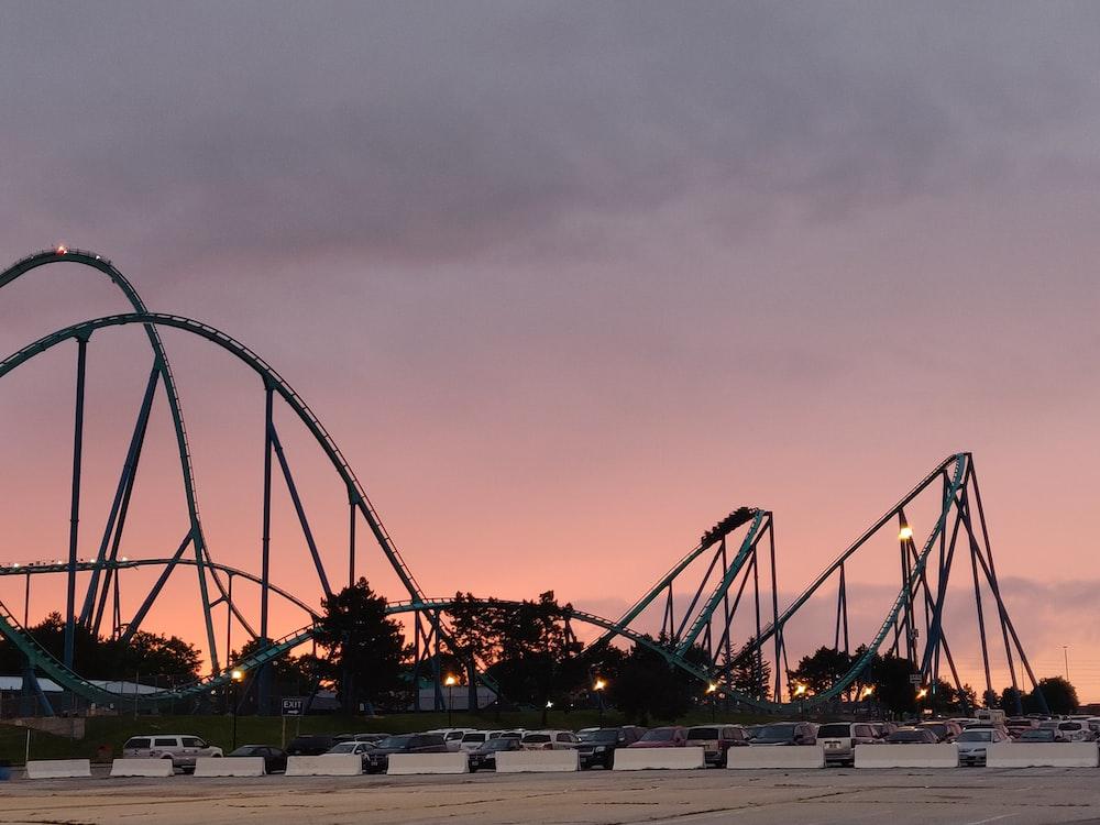 parked car lot beside roller coaster during golden hour
