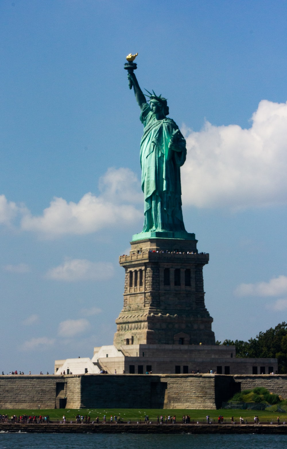 statue of liberty beside a body of water during daytime
