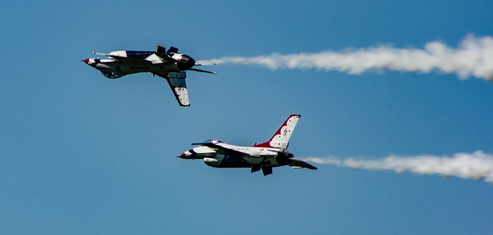 two gray and red air crafts with contrail