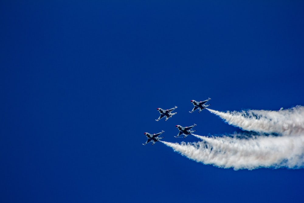 four fighter planes soaring at the sky